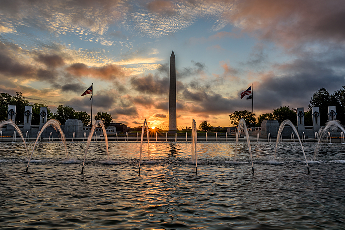 The rising sun burns the sky behind the Washington Monument